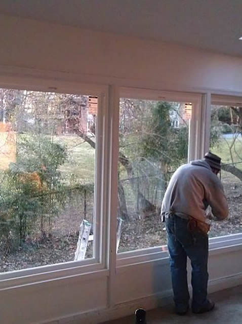worker inside house installing picture windows
