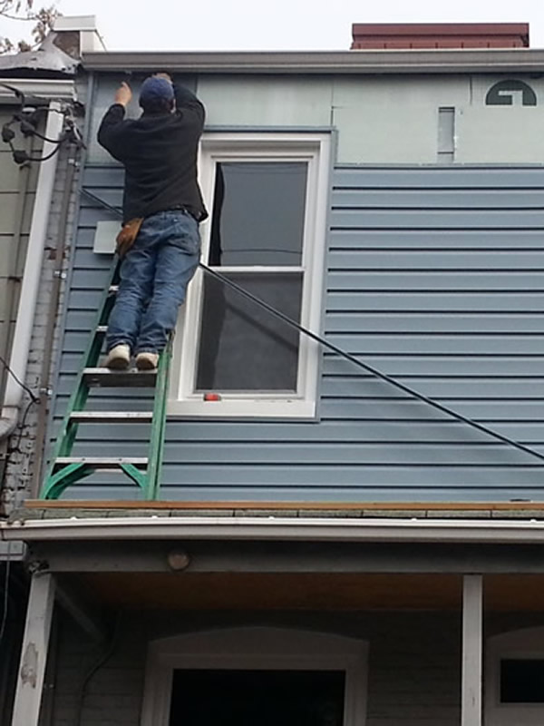 worker on ladder replacing exterior siding