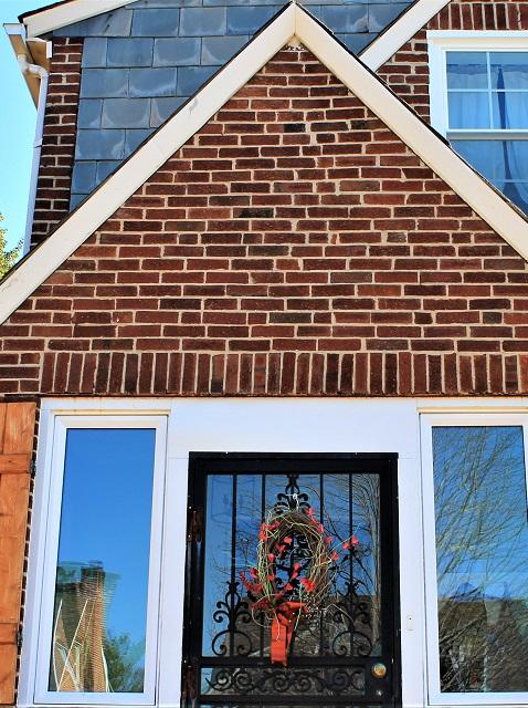 picture windows with wooden shutters surrounding door entryway