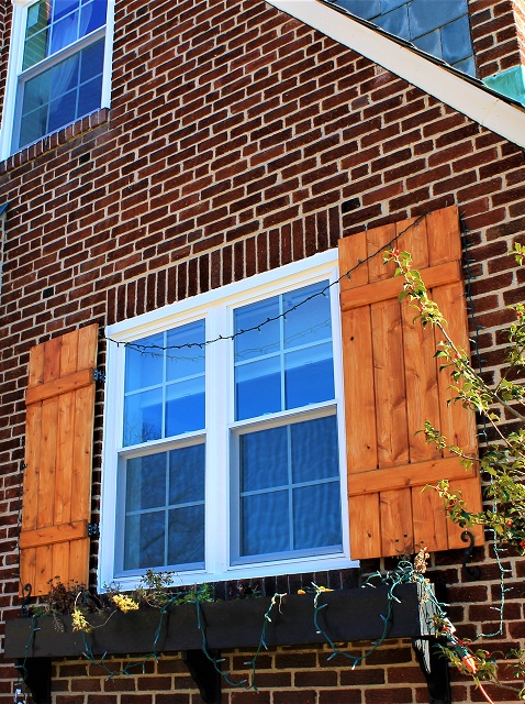 double windows with wooden shutters with brick facade